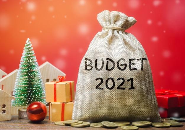 Geldzak budget 2021, kerstboom, huizen en cadeaus. geld verzamelen en een budget plannen. Premium Foto