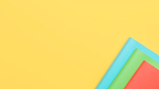 Gele achtergrond met vellen papier in de hoek Gratis Foto