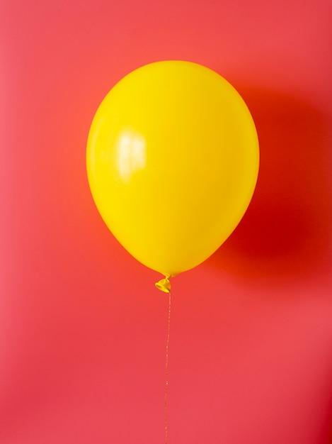 Gele ballon op rode achtergrond Gratis Foto
