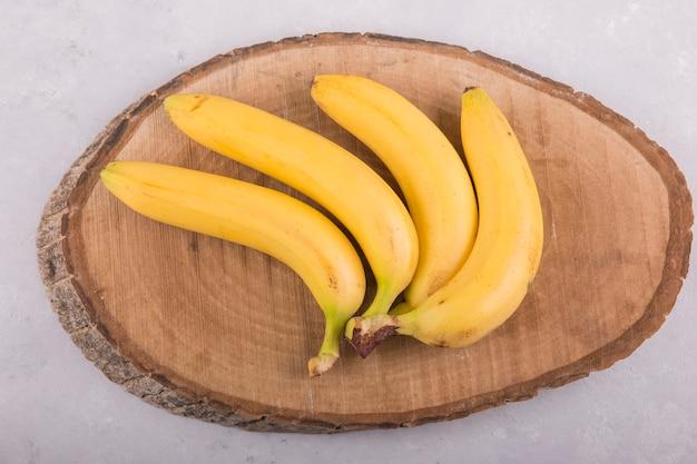 Gele bananen bos geïsoleerd op beton op een stuk hout Gratis Foto