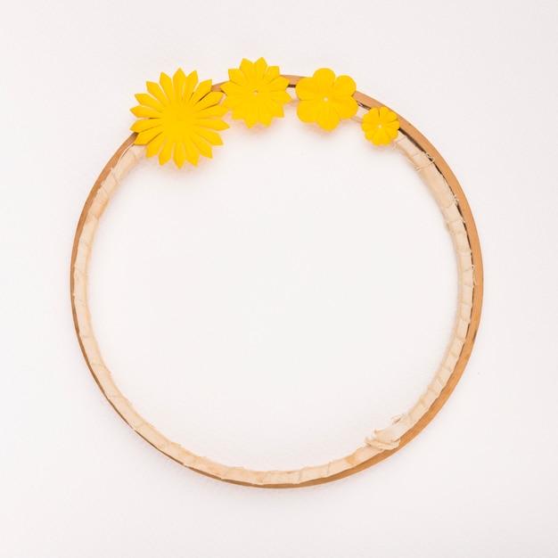 Gele bloemen die op cirkelvormig houten frame op witte achtergrond worden verfraaid Gratis Foto