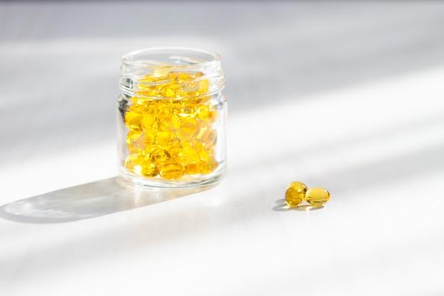 Gele capsules met vitamine d, visolie omega 3 met zonlicht op witte houten achtergrond. gezond en medisch concept. Premium Foto