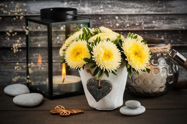 Gele chrysant in concrete pot met kaars Premium Foto
