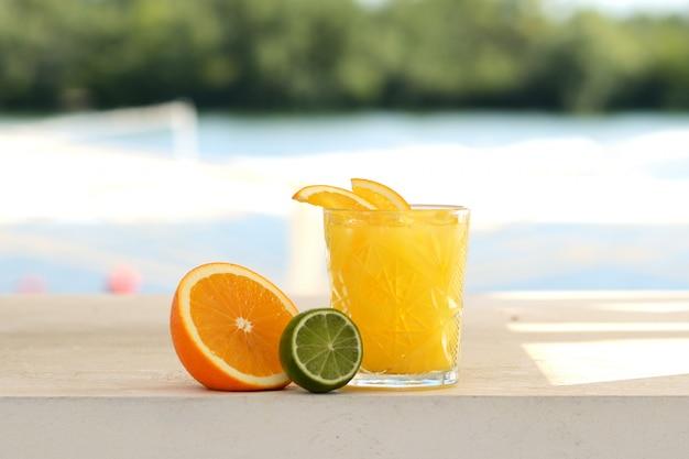 Gele cocktail met sinaasappel, limoen en ijs in een glazen tuimelaar Premium Foto
