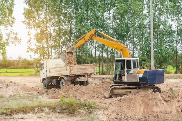 Gele de ladingsgrond van de graafwerktuigmachine in een stortplaatsvrachtwagen bij bouwwerf Premium Foto
