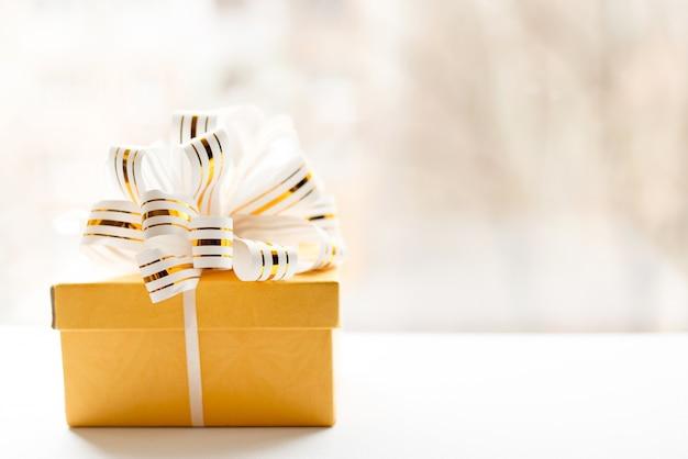 Gele die giftdoos in wit en gouden gestreept lint op lichte achtergrond wordt verpakt. Premium Foto
