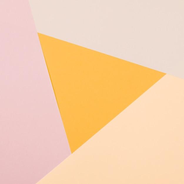 Gele driehoek met kleurrijke papier geometrische plat lag achtergrond Gratis Foto