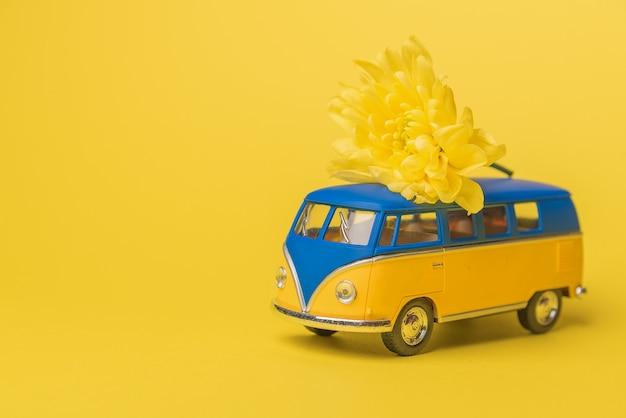Gele en blauwe retro stuk speelgoed bus die een boeket van chrysantenbloemen levert op een gele achtergrond. reizen concept Premium Foto