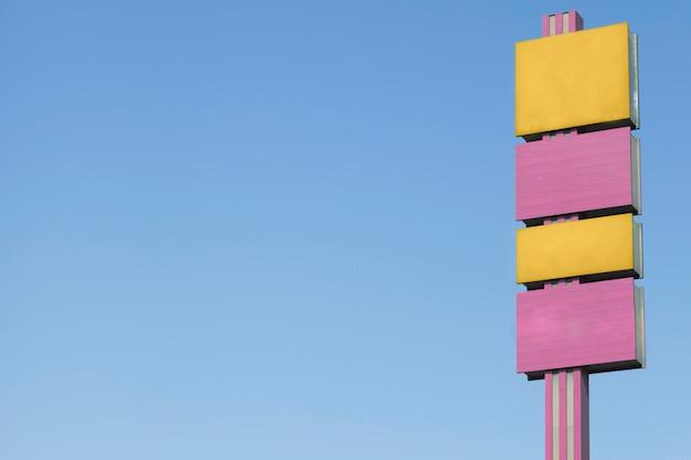 Gele en roze aanplakborden tegen blauwe hemel Gratis Foto