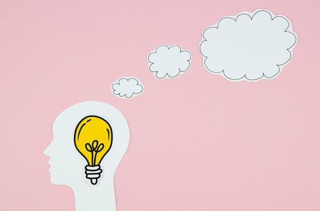Gele gloeilamp in een hoofd met een tekstballon Gratis Foto