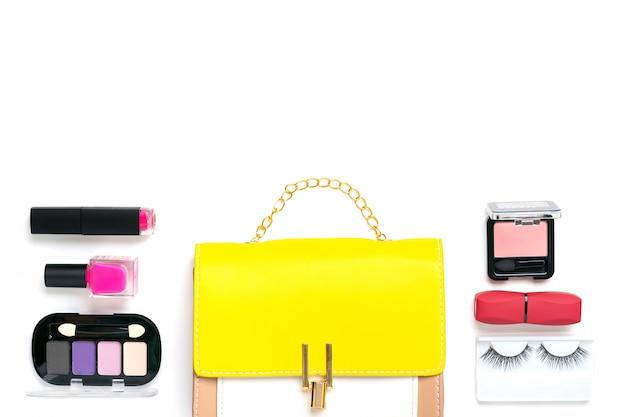 Gele handtas met accessoires voor vrouwen. zonnebril, lippenstift, blush, scrunchy, geïsoleerde borstels. bovenaanzicht plat leggen Premium Foto