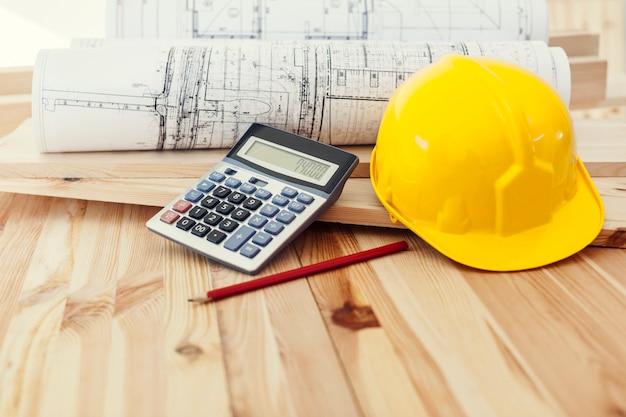 Gele helm met blauwdrukken en rekenmachine op hout Gratis Foto