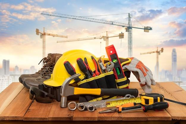 Gele helm voor bouwwerkzaamheden en gereedschappen met een achtergrondkraan. Premium Foto