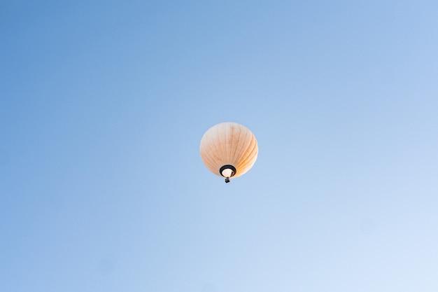 Gele hete luchtballon die in duidelijke blauwe hemel vliegt Gratis Foto