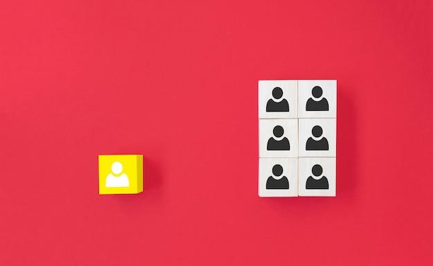 Gele houten kubus met persoonspictogram onderscheiden zich van de menigte op blauwe achtergrond Premium Foto
