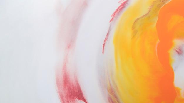 Gele inkt die op witte schuimachtergrond oplost Gratis Foto