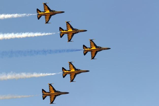 Gele jets manoeuvreren in de lucht tijdens een luchtparade Gratis Foto