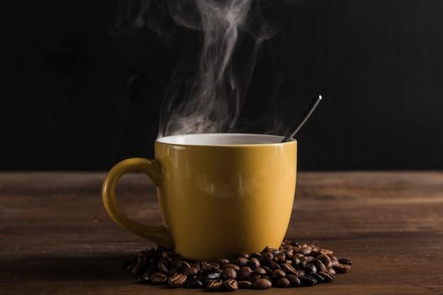 Gele kop met lepel en koffiebonen Gratis Foto