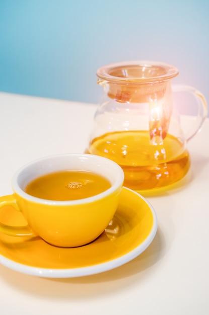 Gele kop thee en glastheepot op de lijst. blauwe achtergrond Premium Foto
