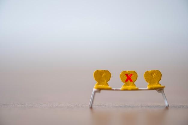 Gele miniatuurstoel met het rode kruis-teken om te verbieden, gaat zitten om afstand te houden bij het publiek en om te voorkomen dat de covid-19-coronavirus-uitbraak een pandemische infectie verspreidt. Premium Foto
