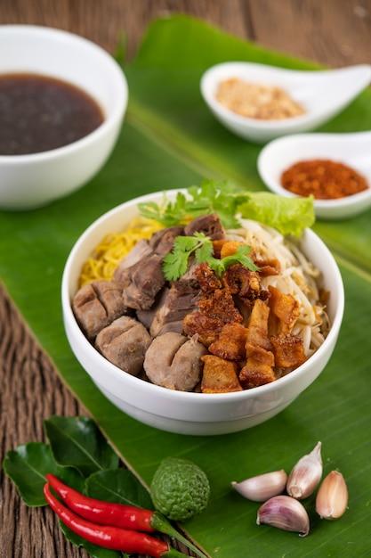Gele noedels in een kopje met knapperig varkensvlees, plakjes varkensvlees en gehaktballen samen met thaise noedels in voedselstijl Gratis Foto