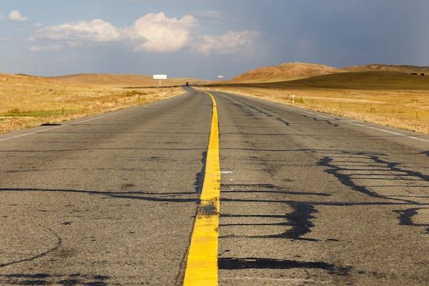 Gele ononderbroken strook op de asfaltweg Premium Foto