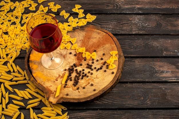 Gele pasta rauw samen met peper en fles wijn op een ronde houten bureau op een bruine tafel Gratis Foto