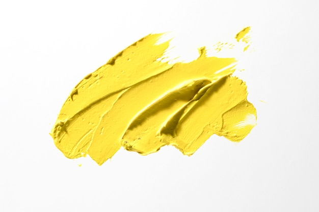 Gele penseelstreek op witte achtergrond Gratis Foto