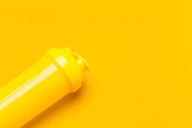 Gele plastic eiwit shaker op levendige achtergrond Premium Foto