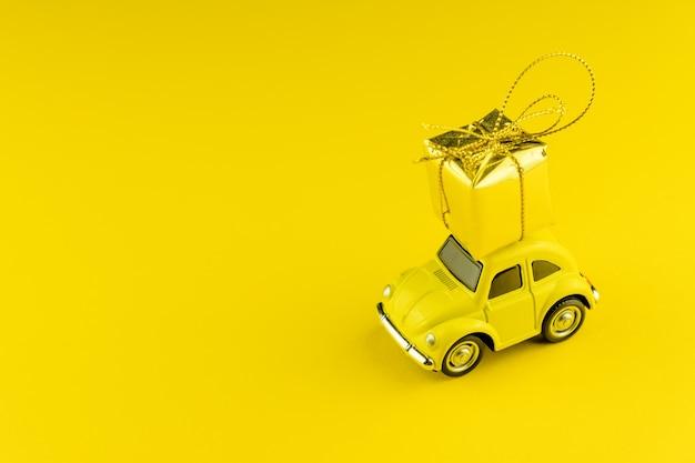 Gele retro auto met gouden geschenkdoos op een dak Premium Foto