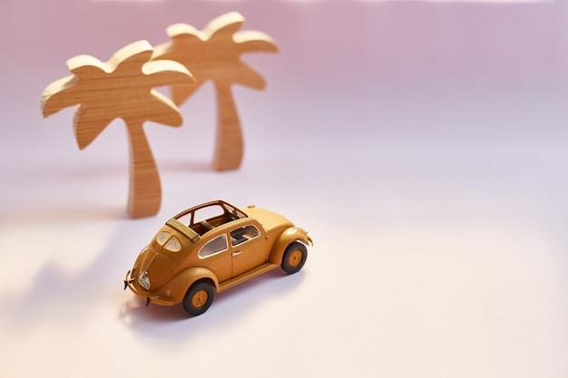 Gele retro cabriolet stuk speelgoed auto en palmen op een roze achtergrond Premium Foto