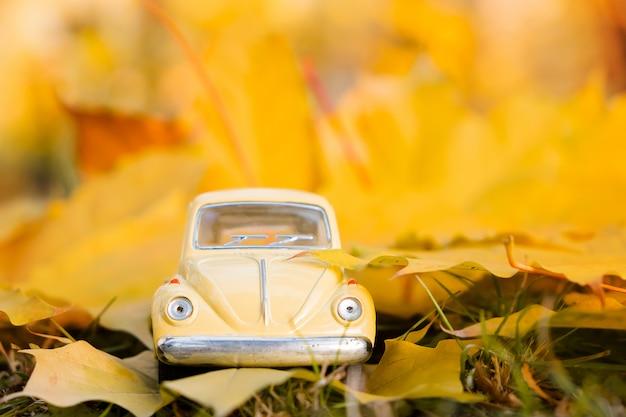 Gele retro speelgoedauto op het blad van de de herfstesdoorn. herfst reizen en vakantie concept. Premium Foto