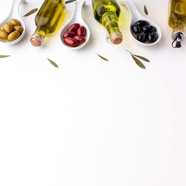 Gele rode zwarte olijven in lepels met bladeren en olieflessen met exemplaarruimte Gratis Foto