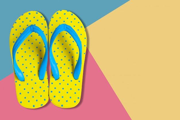 Gele sandalen op roze en blauwe kleuren vlakke achtergrond, leggen foto Premium Foto