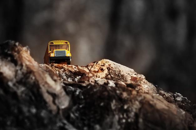 Gele schoolbus (speelgoedmodel) die de landweg kruist. Premium Foto