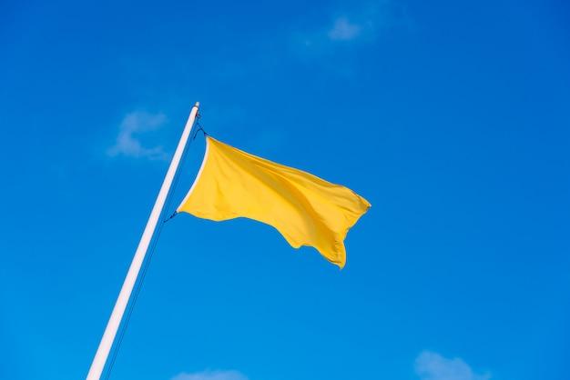 Gele stoffenvlag die aan de wind met de achtergrond van een duidelijke hemel met witte wolken golft. Premium Foto