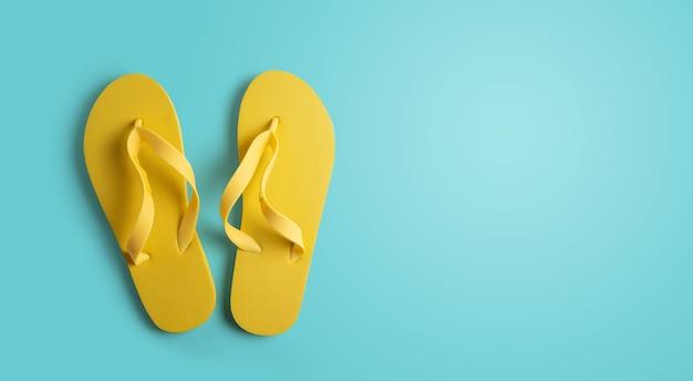 Gele strand pantoffels geïsoleerd op blauw Premium Foto