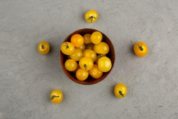 Gele tomaten een bovenaanzicht van verse rijpe vitamine rijk binnen bruine ronde pot op het licht Gratis Foto