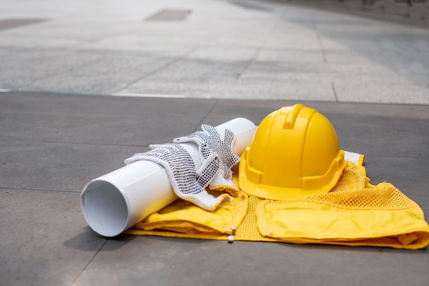Gele veiligheidshelm met handschoen, blauwdruk op vest op vloer Premium Foto