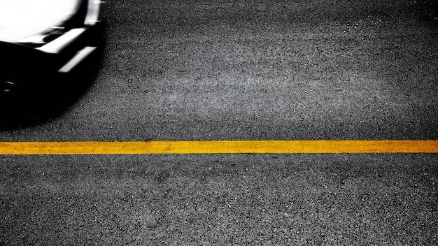 Gele verflijn op zwart asfalt Premium Foto