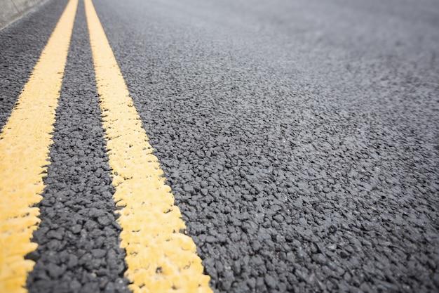 Gele wegmarkering op wegdek Gratis Foto