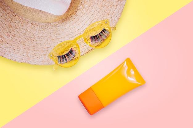 Gele zonnebril met nepwimpers op strohoed en zonnescherm spf room op roze achtergrond. Premium Foto