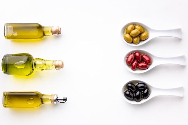 Gele zwarte rode olijven in lepels met bladeren en olieflessen Gratis Foto