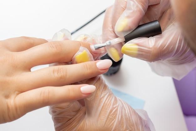 Gellak op de nagels aanbrengen. schellak. manicure maakt manicure in de salon. natuurlijke kleurvernis. nude tint Premium Foto