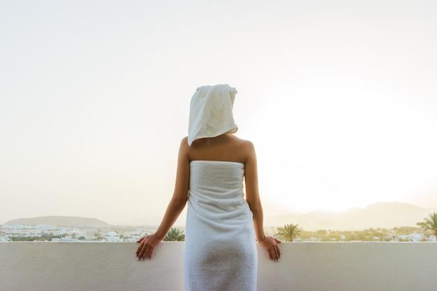Gelooide tedere meid staat op het terras Premium Foto