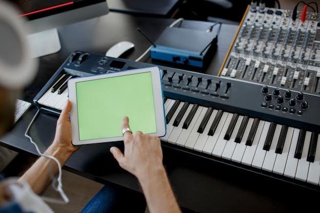 Geluidstechnicus werkt aan mengpaneel in de opnamestudio en houdt een tablet vast Premium Foto