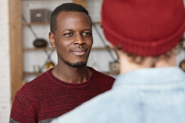 Gelukkig aantrekkelijke afro-amerikaanse jonge man lacht vrolijk tijdens een goed gesprek Gratis Foto