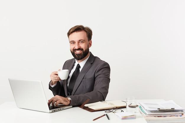 Gelukkig aantrekkelijke bebaarde zakenman met kort bruin haar kopje thee houden en vreugdevol naar de voorkant kijken, werken met laptop en brief aan zijn partners typen Gratis Foto