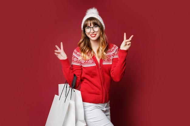 Gelukkig aantrekkelijke vrouw in witte wollen muts en rode winter trui poseren met boodschappentassen Gratis Foto