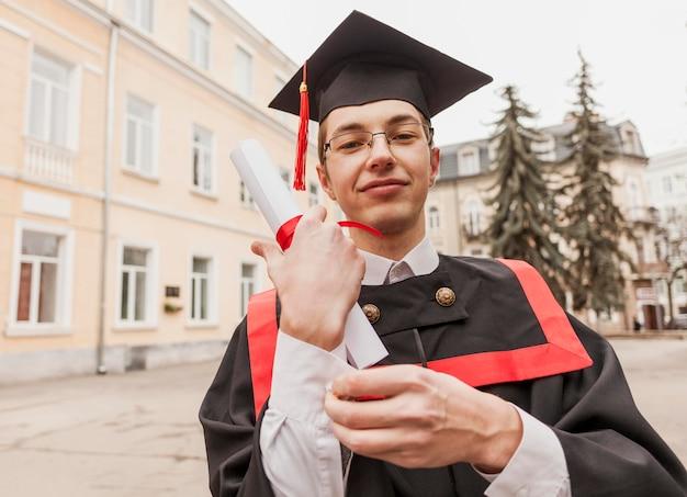 Gelukkig afgestudeerd student met diploma Gratis Foto